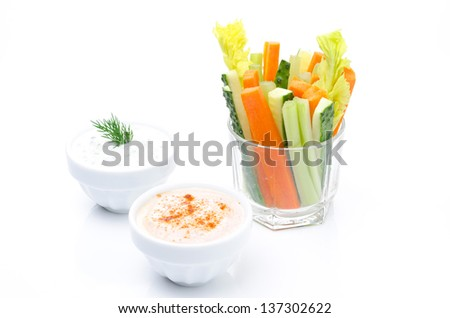 Assorted fresh vegetables in a glass (celery, cucumber and carrot) and two yogurt sauce isolated on white, closeup