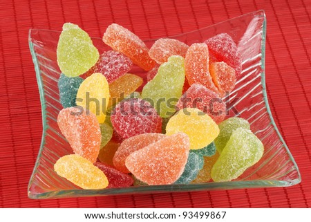 Assorted fruit shaped and flavored jellies in a transparent glass bowl over a red background