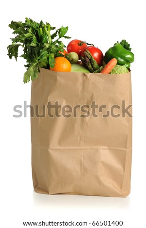 Assorted fruits and vegetables in brown grocery bag isolated over white background