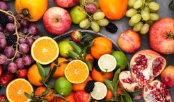 Assorted fruits. Different fruits on a gray background, the whole surface is covered with citrus fruits, pomegranates, apples, grapes, strawberries. Top view