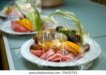 Assorted fruits, wrapped in plastic wrap .