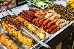 Assorted German sausages grilled in a steel container. Street food market