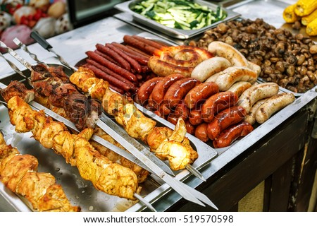 Assorted German sausages grilled in a steel container. Street food market #519570598