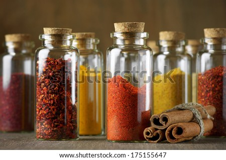Assorted ground spices in bottles and cinnamon sticks on wood.