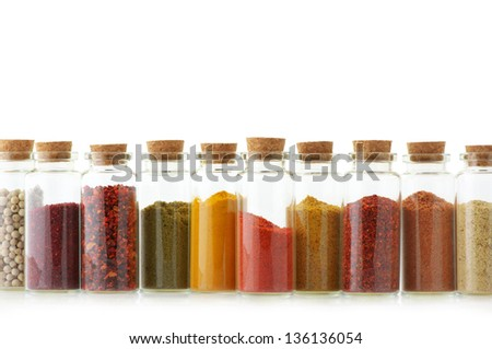 Assorted ground spices in bottles on white background.