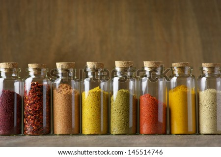 Assorted ground spices in bottles on wooden background.