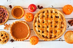 Assorted homemade autumn pies. Apple, pumpkin and pecan. Above view table scene on a white wood background.