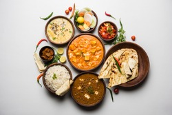 Assorted indian food for lunch or dinner, rice, lentils, paneer butter masala, palak panir, dal makhani, naan, green salad, spices over moody background. selective focus