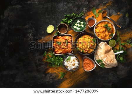 Assorted indian food on black background.. Indian cuisine. Top view with copy space