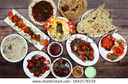 Assorted indian food on wooden background. Chicken Tikka, chicken biryani,chilli chicken, chicken manchurian,tandoori chicken,kulcha, paratha and jeera rice.. Dishes and appetizers of indian cuisine.