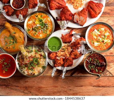 Assorted indian foods chicken biryani,chicken korma,chicken lollipop, paneer butter masala and tandoori chicken on wooden background. Dishes and appetizers of indian cuisine