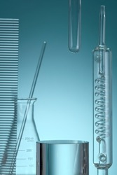 Assorted laboratory glassware equipment showcase with oil on Blue backround. Stage showcase cosmetics on glass pedestal modern in laboratory equipment. Minimal concept.