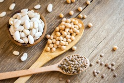 Assorted Legumes (chickpeas, green lentils, white beans) over rustic wooden background - ingredient for healthy vegan, vegetarian, diet food meal, vegetable protein