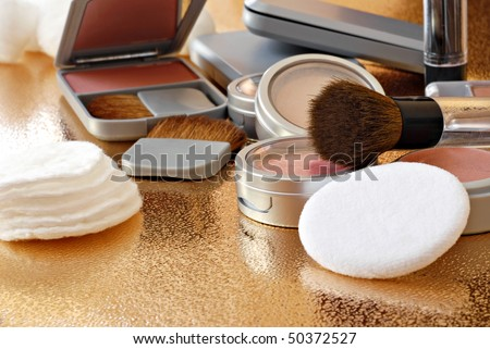 Assorted makeup products with brushes and applicators on shiny gold background.  Macro with shallow dof.