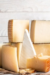 assorted manchego cheese on aged table, Various types of cheese composition on a light background, vertical image, place for text.