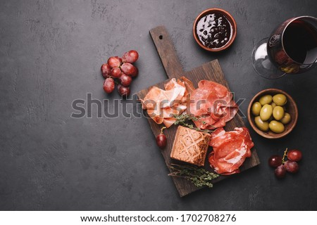 Assorted meat appetizers for wine. Bresaola, prosciutto, pork neck, pate, jam, olives and grapes. Traditional italian meat sausages on black stone background