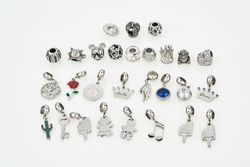 Assorted metal charm pendants for necklace or bracelet. Many charms isolated on white background: crown, cactus, music, rose, key, crystal and etc