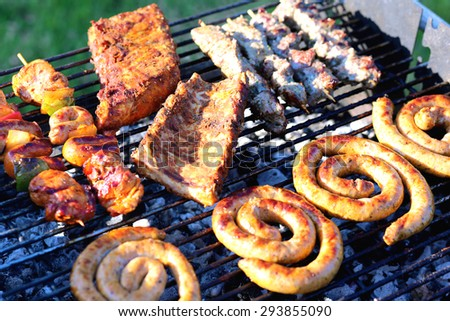 Assorted mixed grill on wooden skewers from chicken meat, lamb and pork, marinated spareribs, sausages and various vegetables roasting on barbecue grid cooked for summer family dinner