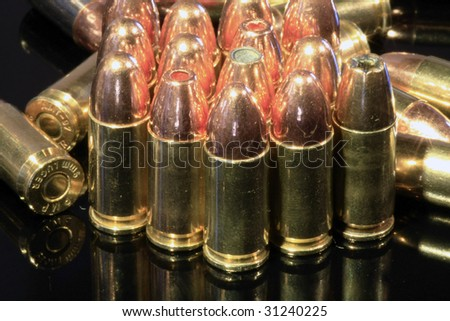 Assorted 9mm bullets isolated on a black reflective surface