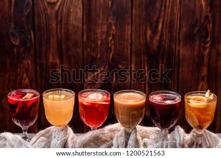Assorted mulled wine. Variety of mulled wine in beautiful glasses standing in a row on a dark wooden background. advertising photo of mulled wine. Close up #1200521563