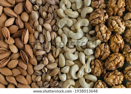 Assorted nuts almonds, pistachio, cashews, walnut. Flatly organic mixed nuts background. Healthy food, useful microelements and vitamins. Useful health snack.Vegetarian snack of different nuts