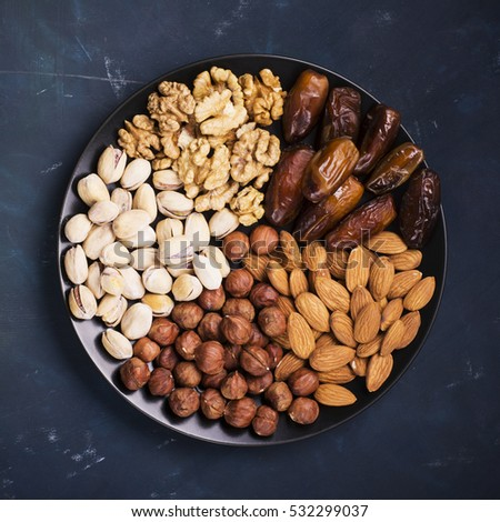 Shutterstock Assorted nuts, almonds, pistachios, walnuts, hazelnuts and figs on a black ceramic plate on a dark background. Top view