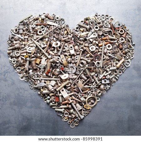 assorted nuts and bolts heart on metal texture background