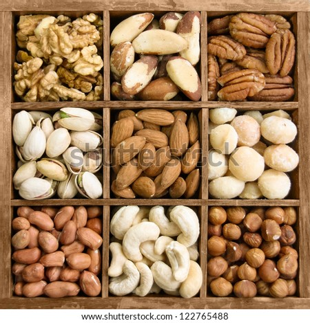 Assorted nuts in a wooden box (from top left: walnut, brazil nut, pecan, pistachios, almond, macadamia, peanut, cashew, hazelnut)