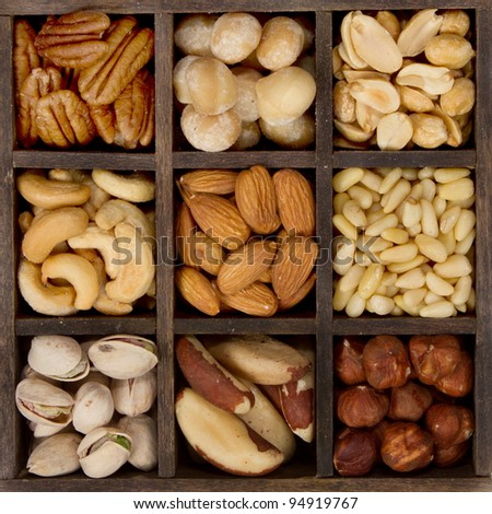 assorted nuts nine varieties for a background in a printers box, almond, cashew, brazil, hazelnut, peanut, pecan, pine, pistachio, macadamia