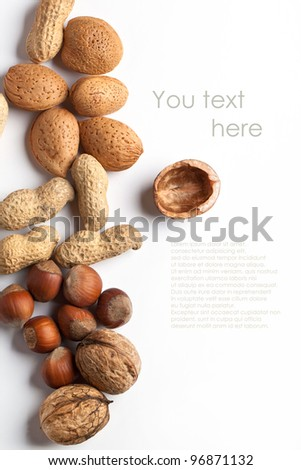 Assorted of whole and chopped nuts almond, hazelnut, walnut and peanut over white with sample text