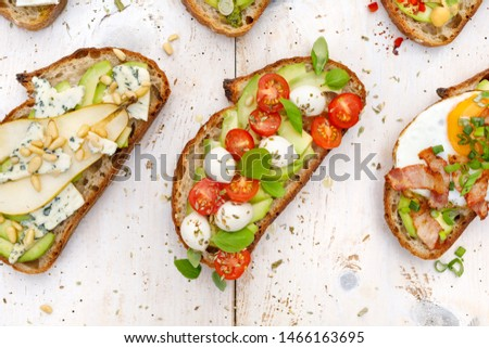 Assorted open faced sandwiches, Open avocado sandwiches made of slices of sourdough bread with various toppings  on a white wooden table, top view. Delicious and nutritious breakfast
