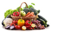 Assorted organic vegetables and fruits in wicker basket isolated on white background.