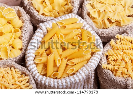 Assorted pasta in burlap bags - top view, closeup