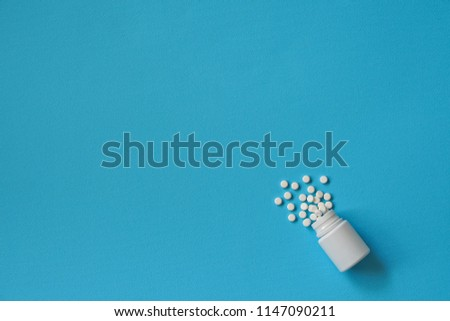 Assorted pharmaceutical medicine pills, tablets and capsules and bottle on blue background. Drugs and various narcotic substances. Copy space for text. Stock photo for design