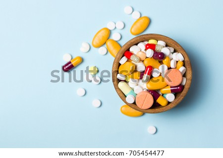Assorted pharmaceutical medicine pills, tablets and capsules on wooden bowl
