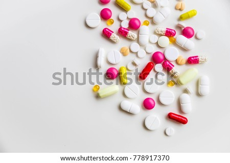 Assorted pharmaceutical medicine pills, tablets and capsules.Pills background. Heap of assorted various medicine tablets and pills different colors on white background. Health care.Top view.Copy space
