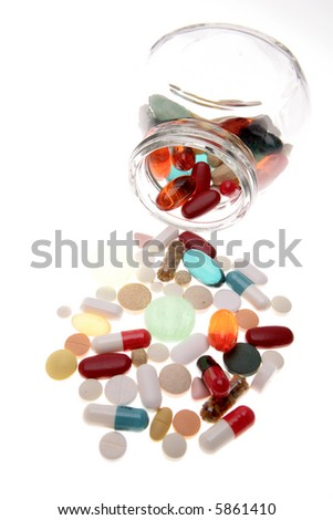 Assorted pills spilling from jar