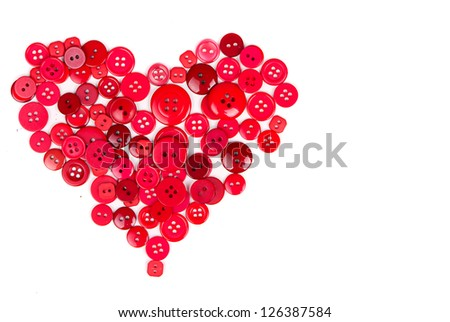 Assorted red buttons in shape of heart on white background
