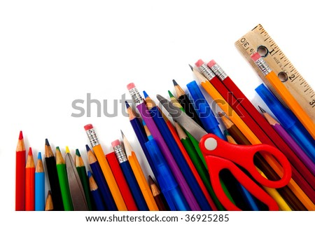Assorted school supplies including pencils, pens, scissors and rulers on a white background with copy space