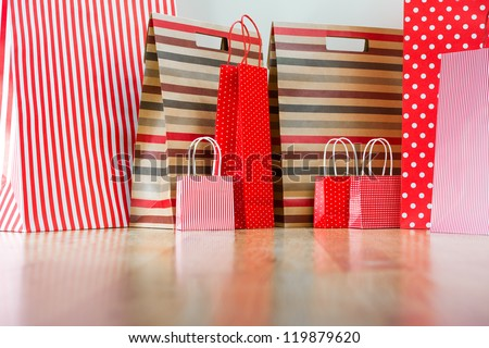 Assorted shopping and gift red paper bags - shopping and holiday concept with copyspace