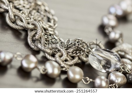 Assorted silver costume jewellery with a jumbled pile of chains with different shaped links, a clear crystal bead and a necklace of round silver beads with focus to the chains