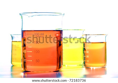 Assorted sizes laboratory glass scientific beakers filled with orange and yellow chemical liquids before a chemistry experiment in a science research lab
