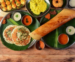 Assorted South indian breakfast foods on wooden background. Ghee dosa, uttappam,medhu vada,pongal,podi idly and chutney.. Dishes and appetizers of indian cuisine