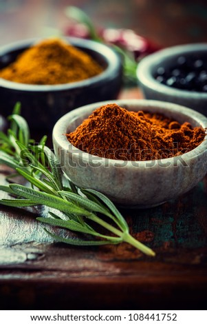 Assorted spices in small containers and rosemary on wooden background