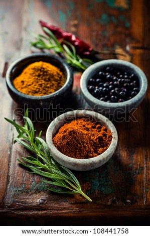 Assorted spices in small containers and rosemary on wooden background - stock photo