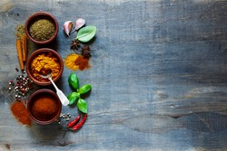 Assorted spices in small wooden bowls. Food and cuisine ingredients. Cooking background with space for text.