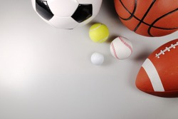 Assorted sports balls including a basketball, american football, soccer ball, tennis ball, baseball and golf ball on white background, top view.