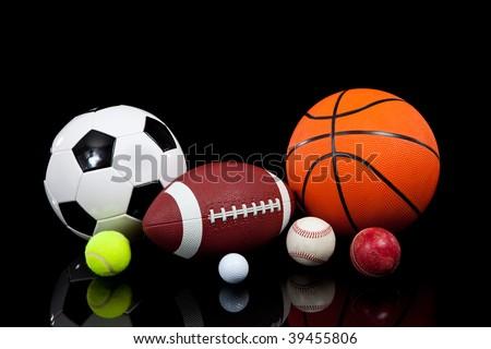 Assorted sports balls including a basketball, american football, soccer ball, tennis ball, baseball, golf ball and cricket ball on a black background