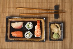 Assorted sushi dishes with wooden chopsticks on wooden place mat