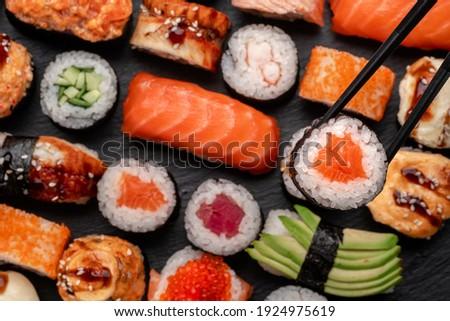 Assorted sushi nigiri and maki big set on slate. A variety of Japanese food with tuna, crab, salmon, eel and rolls. Take sushi in chopsticks